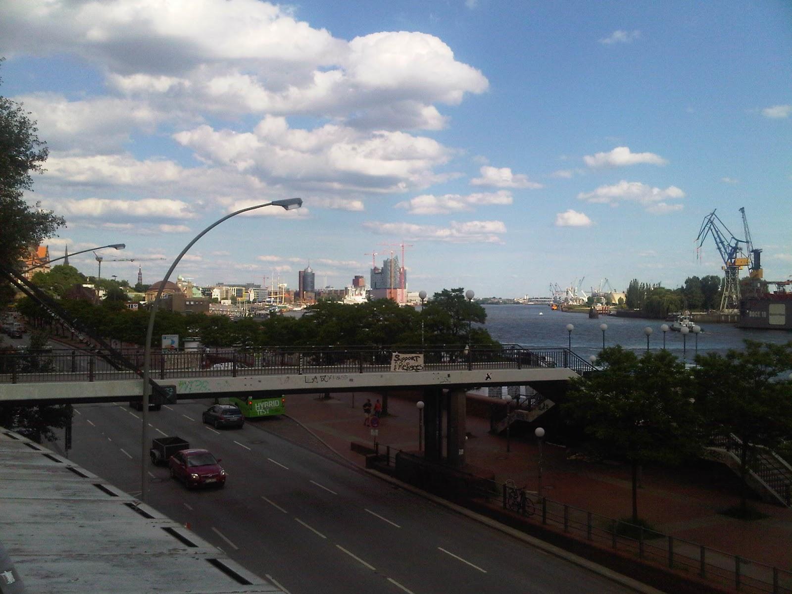 Blick elbaufwärts in den Hafen hinein. Hafenstraße, Brücke, Wolken, blauer Himmel. Kräne.