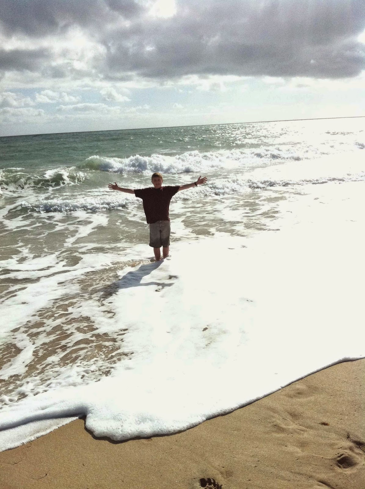Boy with feet in the ocean smiling  and arms sppread wide apart