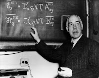 Niels Bohr standing next to a blackboard with equations on it.