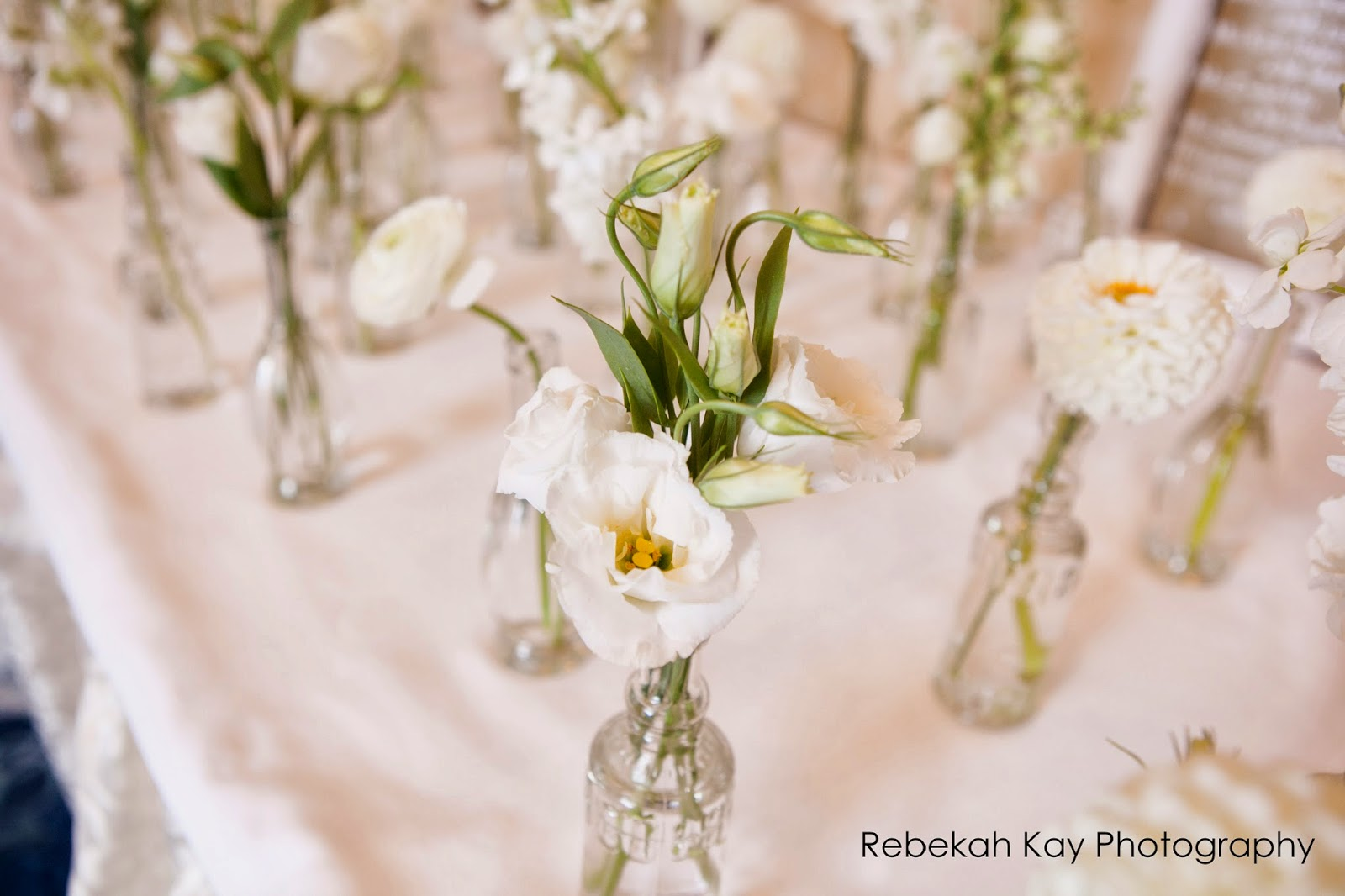 les fleurs : bud vase escort cards : white flowers place card table : bud vase favors