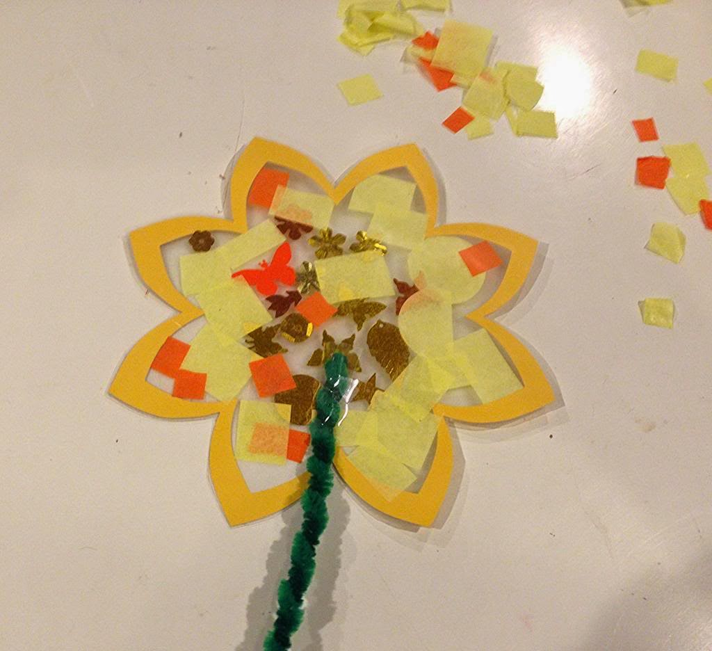 Contact paper flowers munchkins and mayhem contact paper is cut into a flower shape for a fun springtime craft with dolen diaries she then lets the kids stick on pieces of tissue paper and sparkly jeuxipadfo Image collections
