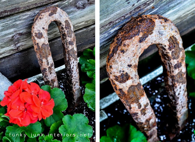 rusty junk as garden art in a flowerbed