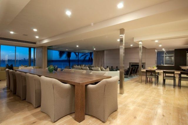 Photo of two large dinning tables and living room in the background