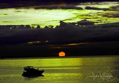 Cruise ship sailing towards the horizon with the setting sun at Manila Bay