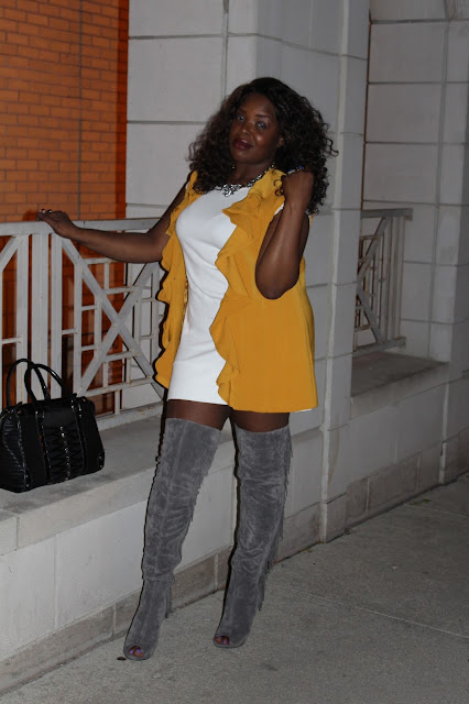 Gold-ruffled-blazer-altered-into-a-vest-worn-with-simple-all-white-mini-dress-and-gray-suede-over-the-knee-boots