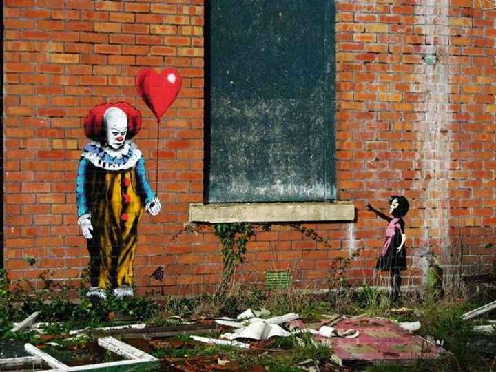street art clown ça avec ballon et petite fille sur mur de brique