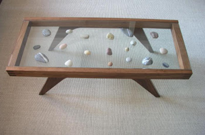 coffee table with collection displayed between two pieces of glass