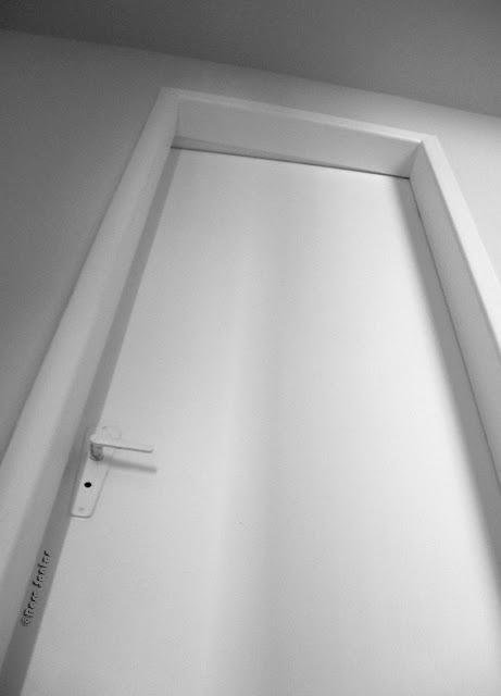 Fotografia P&B. É vista de baixo para cima, em quase sua totalidade, uma porta aproximadamente fechada. A imagem da porta está mais larga em baixo afinando-se para cima. A porta e parte do teto escurecido estão levemente inclinados para a direita da imagem, mais claras estão as paredes ao redor da porta, e quase brancos, a porta, o trinco no lado esquerdo e os perfis. A iluminação mais clara no lado superior direito e laterais externas dos perfis, mostra a geração de sombra dos perfis e do trinco na porta.