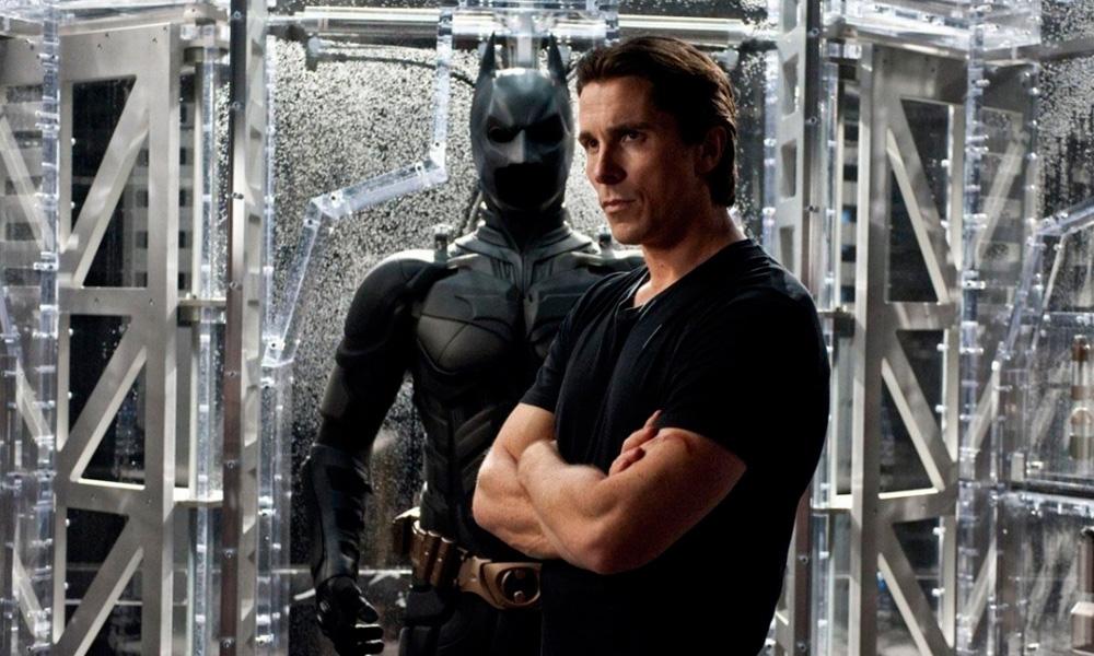 Cena do filme Batman – O Cavaleiro das Trevas Ressurge (2012) mostrando bruce wane na frente do traje do batmam guardado em um suporte especial transparente