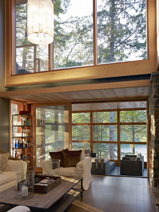 Photo of cozy small living room by the large windows overlooking the forest