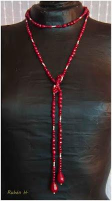 Collar extra-largo realizado en plata y piezas de jade granate de diferentes tamaños y formas. Su diseño y longitud (1.40m), permite colocarlo de diversas maneras como si de un foulard se tratase, incluso se puede utilizar de cinturón joya.
