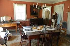 Photo of servants quarters. Simple room, with dining table and many places to sit. Two mannequins displaying clothing of servants in period.