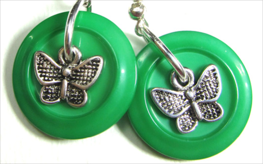 Drop dangle earrings have silver butterfly charms layered over green fashion buttons