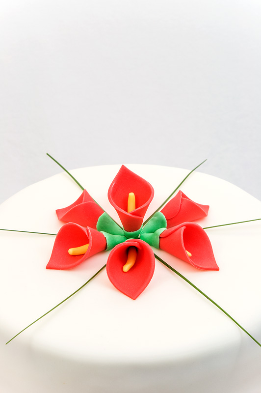 Red calla lily wedding cake fondant chocolate and peach cake close up on top of the cake