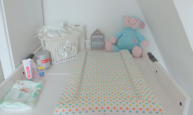 baby changing area with polka dot changing matt, teddy bear and to the moon and back plaque