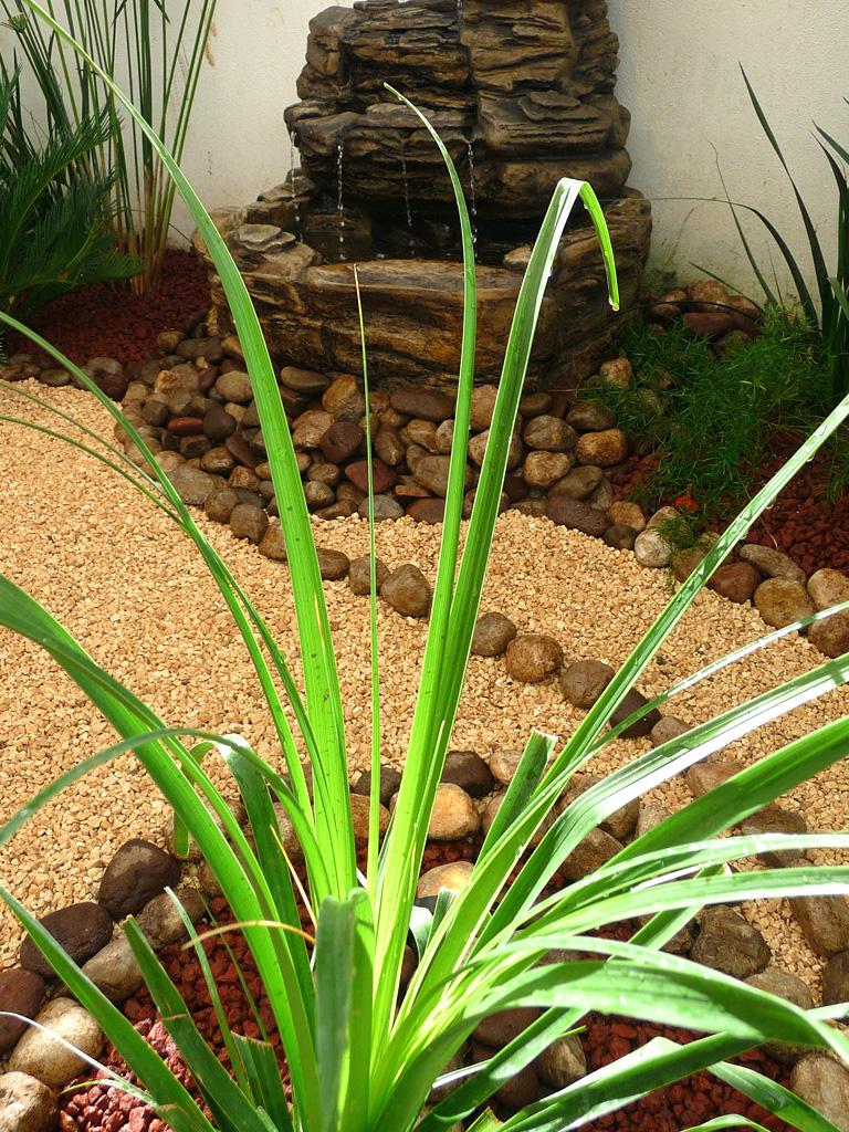 fuente de agua y lamparita en jardin pequeño