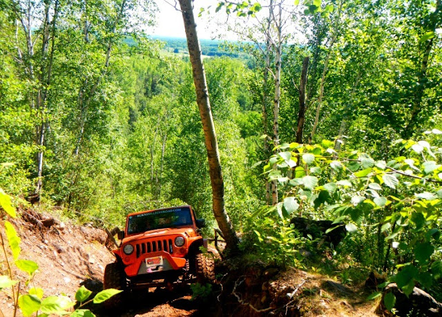 orange jeep climing up a hill in the iron range state recreation area in gilbert minnesota during crawl for the cure