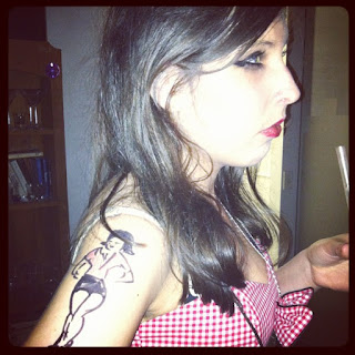 A slim, dark-haired girl in a checked dress, with a poorly drawn sharpie tattoo on her arm.