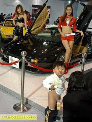 Criança pequena faz xixi em uma garrafa, em feira de automóveis.
