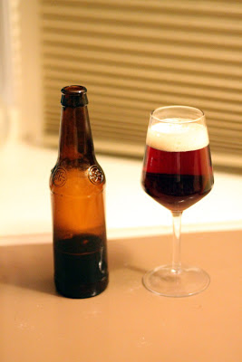 A wine glass of sour beer brewed with buckwheat and flavored with pie cherries.