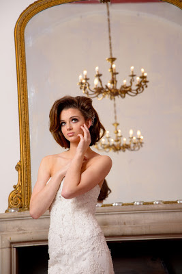 Brunette bride in a white wedding dress standing in front of a gold framed mirror
