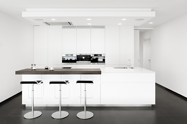 Small white kitchen with three bar chairs