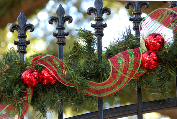 Tinsel tie ball ornaments and deco mesh decorate a wrought iron fleur de lis gate