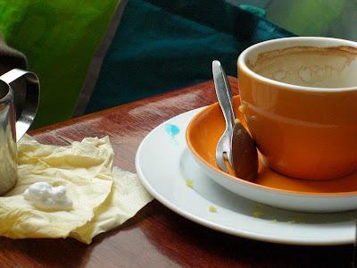 bunte Tasse mit Farbklecksen auf Holztisch