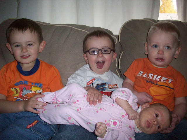 Big Brothers holding Little Sister with funny faces