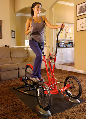 Red StreetStrider on a stand in a living room with woman exercising