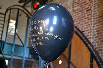 gold writing on black balloon
