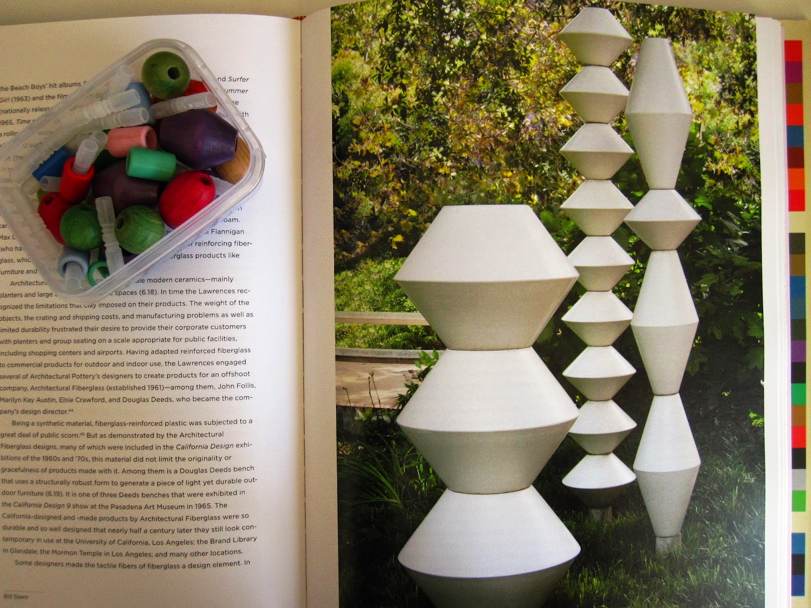 Picture in a book of La Gardo Tackett's garden sculptures, with a container of wooden beads next to it.