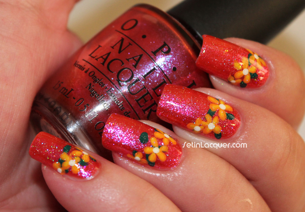 Fun floral nail art. A few orange flowers on a bright shimmery backdrop.