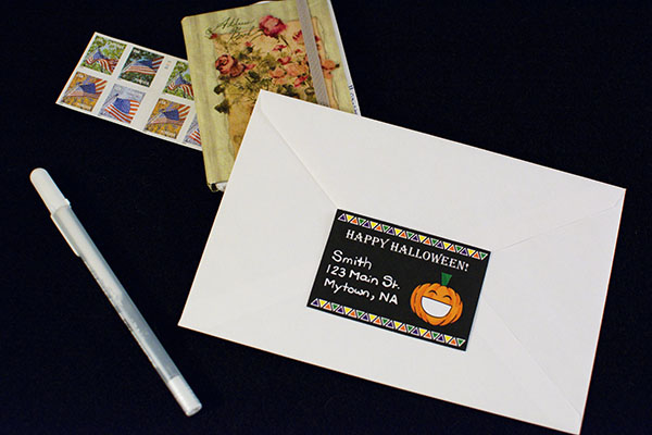 White envelope with smiling pumpkin return address label surrounded by a green address book and a book of American flag forever stamps