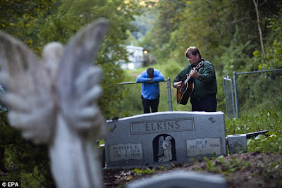 David Payne sings at the gravesite of Bob Elkins.