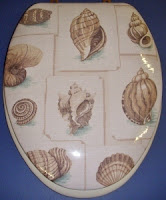 Decorative, hand-upholstered padded toilet seat with sea shells pattern lid.