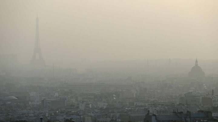 This file picture dated March 11, 2014 shows the Eiffel tower and Paris' roofs through a haze of pollution. Paris is experiencing a periodic pollution spike on March 18, 2015. (Credit: © Patrick Kovarik, AFP) Click to Enlarge.