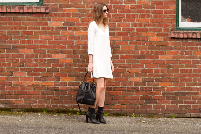Vancouver fashion blogger, Alison Hutchinson, is wearing a white Zara dress, black Vince boots, a black leather Madewell bucket bag, and YSL sunglasses from Smart Buy Glasses