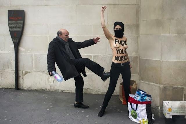Мужчина бьет ногой активистку группы Femen во время одной из их акций в Париже