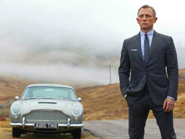 Daniel Craig as James Bond standing in front of his Aston Martin in Skyfall movieloversreviews.blogspot.com