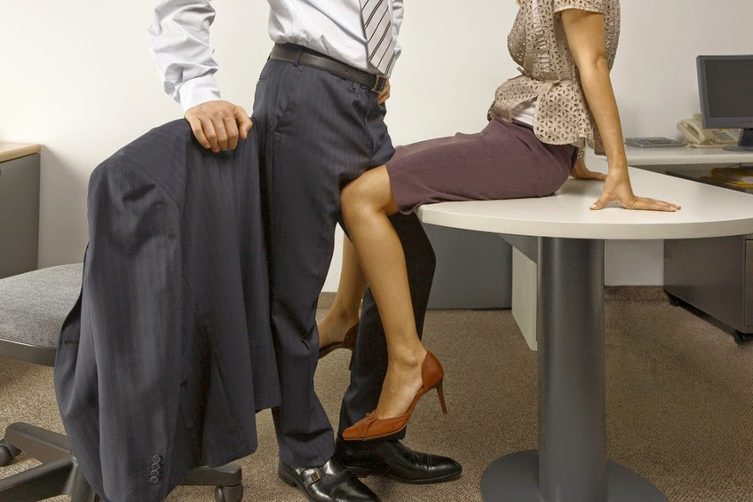 Low section view of a businessman and a businesswoman flirting in an office