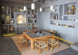 the design of built in wall shelf meets the side of the dining room equipped with items inspired by asian designs in it the gray color seems to envelop