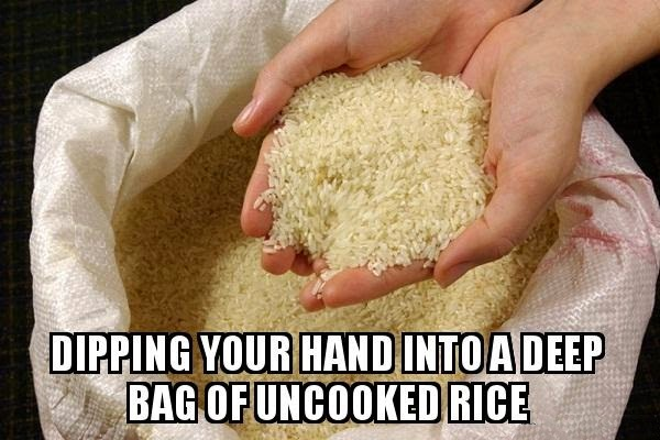 dipping hand in uncooked rice