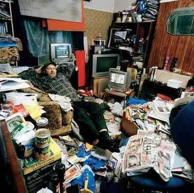 Homem em escritório abarrotado de papeis, sujo e desorganizado.