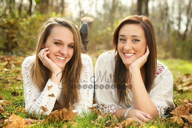 two teen girls laying on the ground wearing white shirts with fall leaves around them