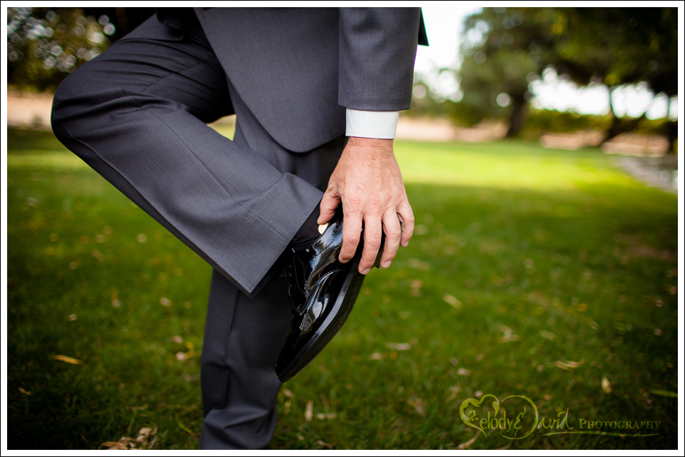 Groom putting his lucky penny in his shoe