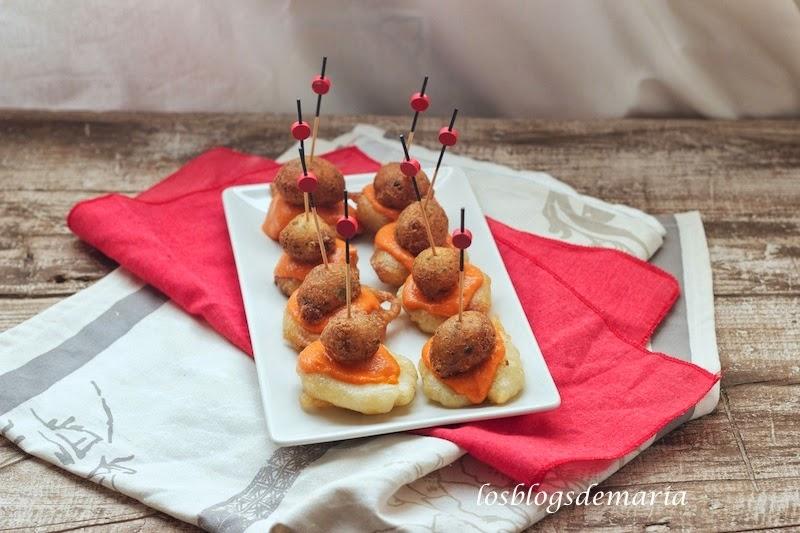 Aperitivos de buñuelos de bacalao sobre berenjena en tempura y salmorejo
