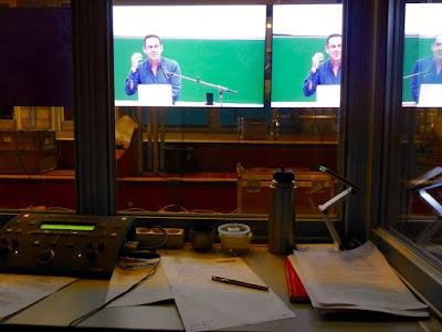 Blick aus der Kabine, über Technik und Papier hinweg, auf einen sehr bunten, großen Bildschirm