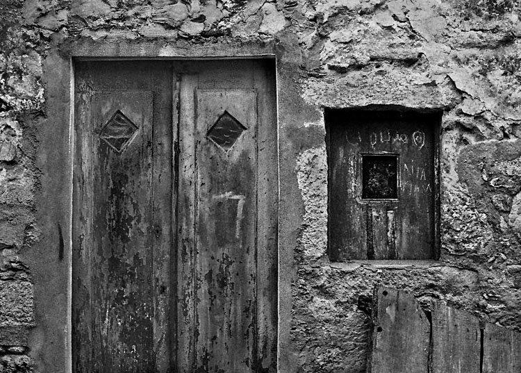 Porta e janelas em madeira velha, numa parede com reboco tosco