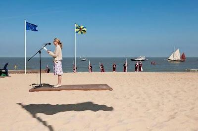 mujer dando un discurso en la playa y parece flotar sobre la arena
